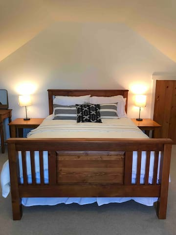 Spacious bedroom upstairs with queen bed, beautiful solid wood frame and hotel rated sheets to cozy up to