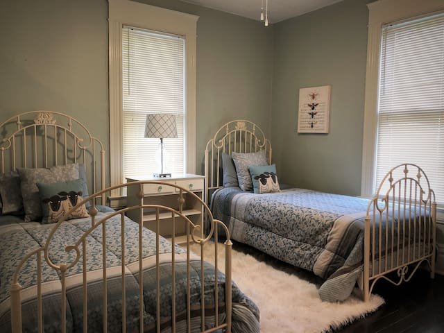 The back bedroom is set up with twin beds and a soothing blue and gray/brown color scheme.