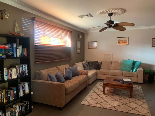 Main loungeroom with a sofa bed and comfy couch, tv with Foxtel, books and games.