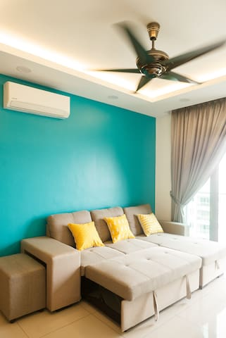 Air conditioned living room with comfortable sofa bed & cushions