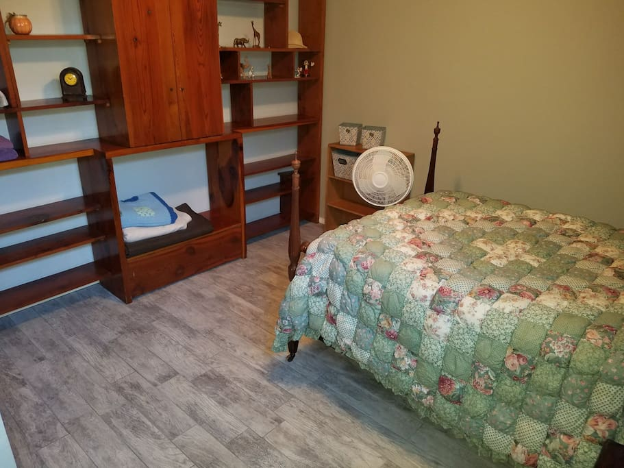 Full size bed, comfortable large room, with tile floor. Shelving unit.