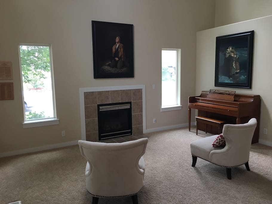 Vaulted entryway room featuring a fireplace and piano. A great place to curl up to a good book.