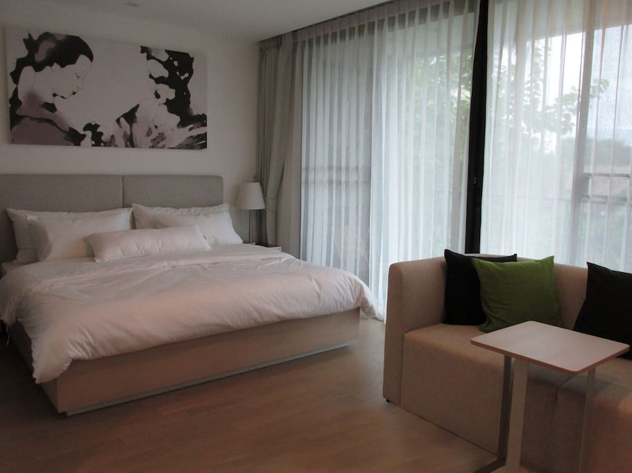 Bedroom with hotel-grade white cotton bed-linens with slidable door to separate from living area when needed