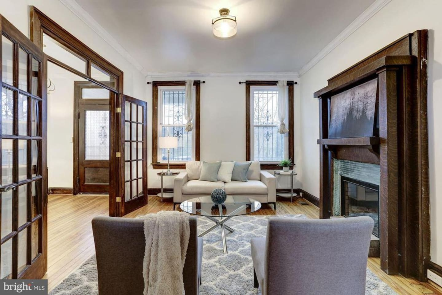 Front foyer which leads to dining room - Original woodwork throughout including pocket doors. Great light through windows
