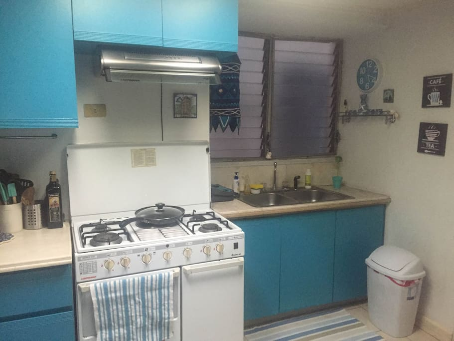 Kitchen complete with microwave, stove and capsule coffee maker.