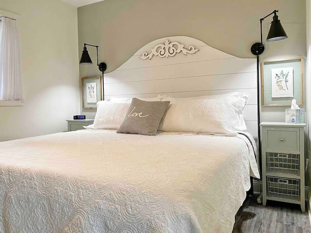 Bedroom with a King size bed. There are swivel arm dimmable lamps on each side of the bed along with night stands.