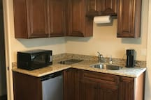 The kitchen is fully equipped and has a microwave, two burner stove top, and a refrigerator /freeze combo; no oven.
