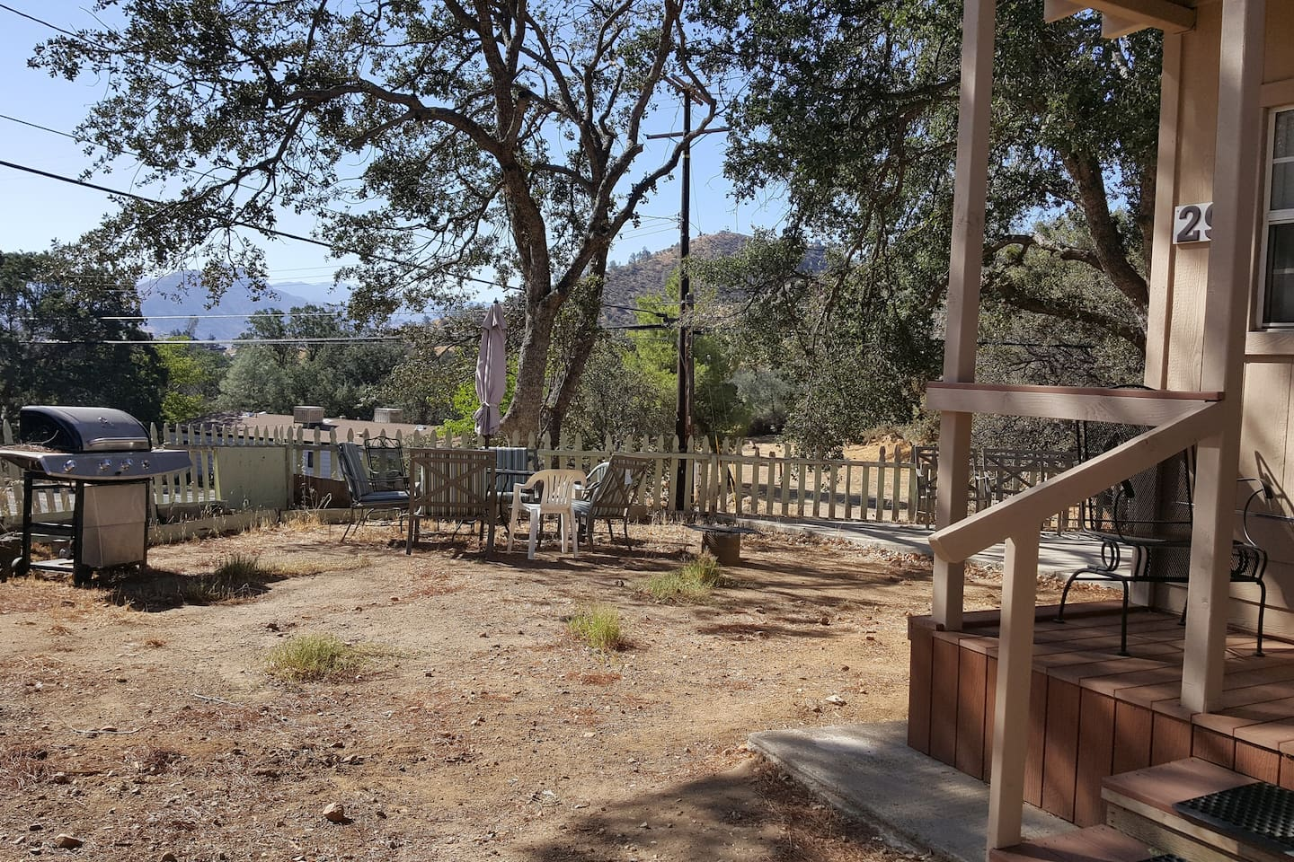 Front yard in in progress, but affords a peek at the lake and comfortable patio furniture, plus portable fire pit.