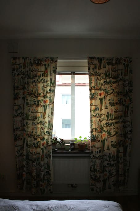 The window in the bedroom has got blinds and curtains