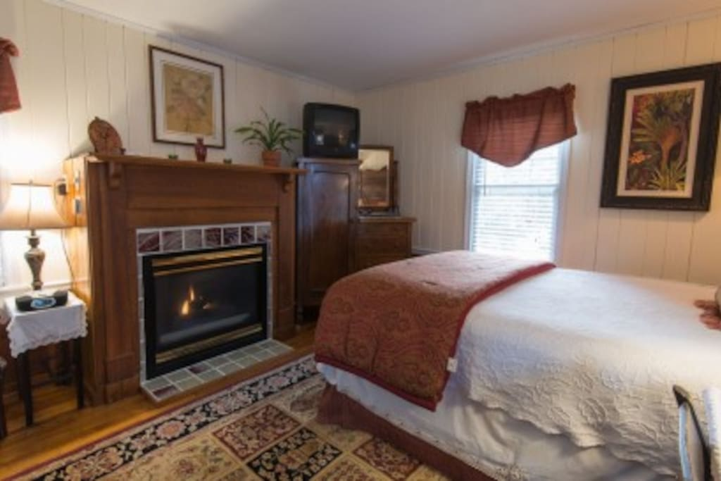 The Forest Room has a queen bed, gas fireplace, window AC and whirlpool tub. It features warm earth tones.