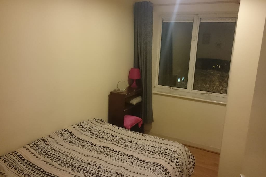 Double bedroom with double bed and heater.