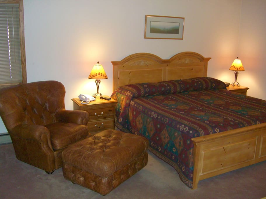 Spacious Master Bedroom with King Bed Leather chair & Ottoman