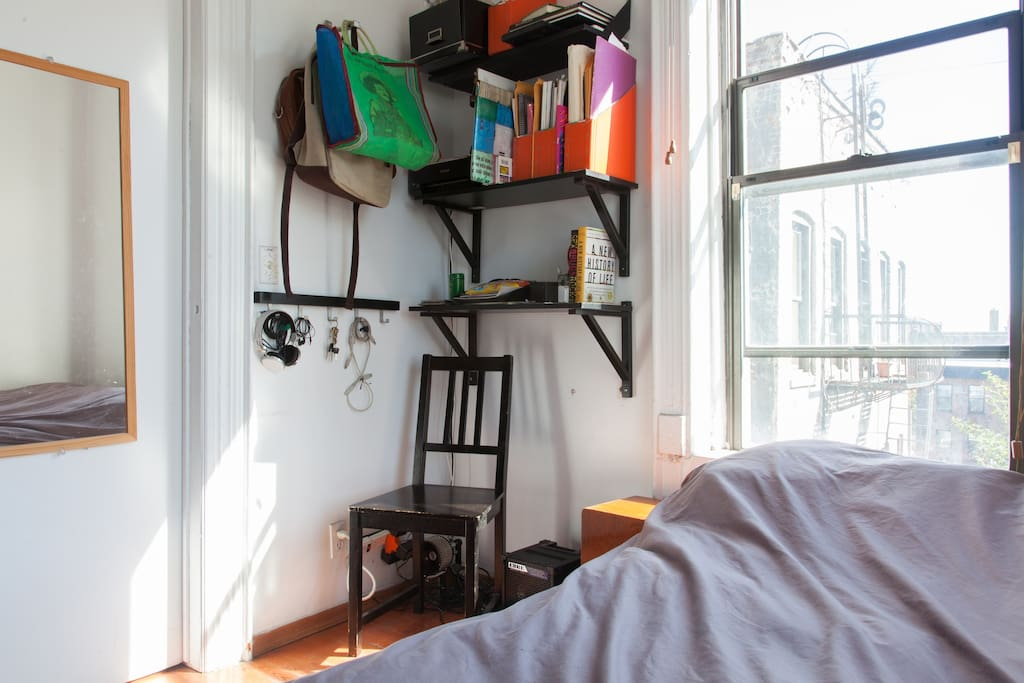 Super sunny bedroom with nice view. It has a closet and shelves.