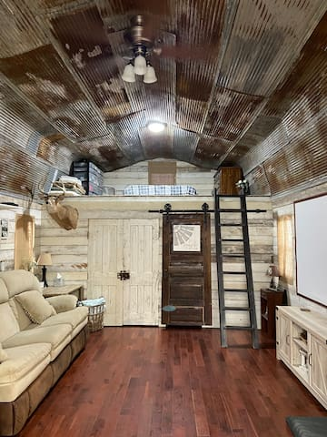 The rustic tin ceiling, old barn wood walls, and all three old doors are from our family farm. Beds are located up in both lofts