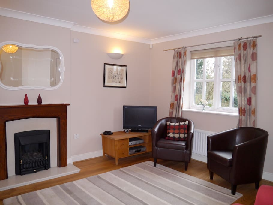 """Cosy lounge with fireplace and 26"""" flat screen TV, overlooking the secluded gardens and the RSC Theater."""