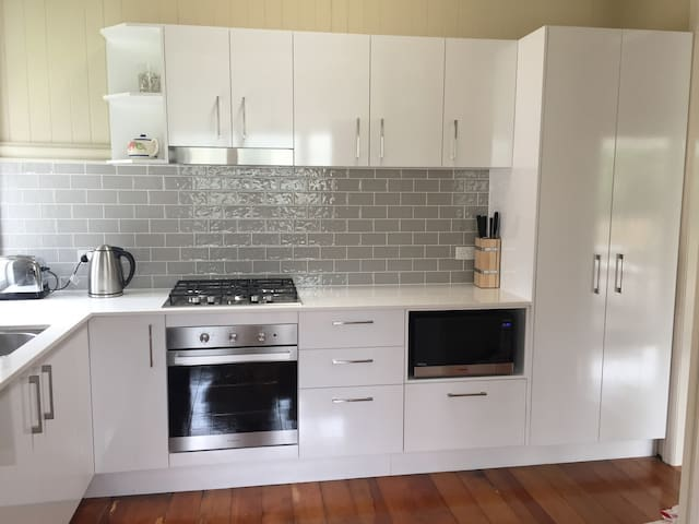 Kitchen - newly renovated with oven, cooktop, fridge and microwave. There is also a coffee machine, toaster and kettle available in the kitchen space.
