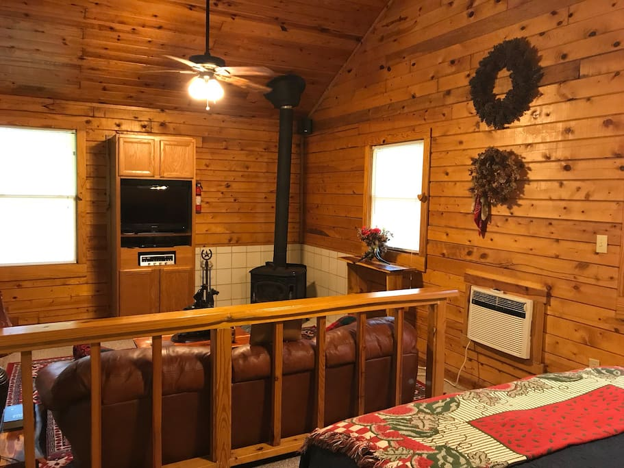 Cabin 1, Rustic Romance has a Step down living room, wood burning stove visible from the bedroom area