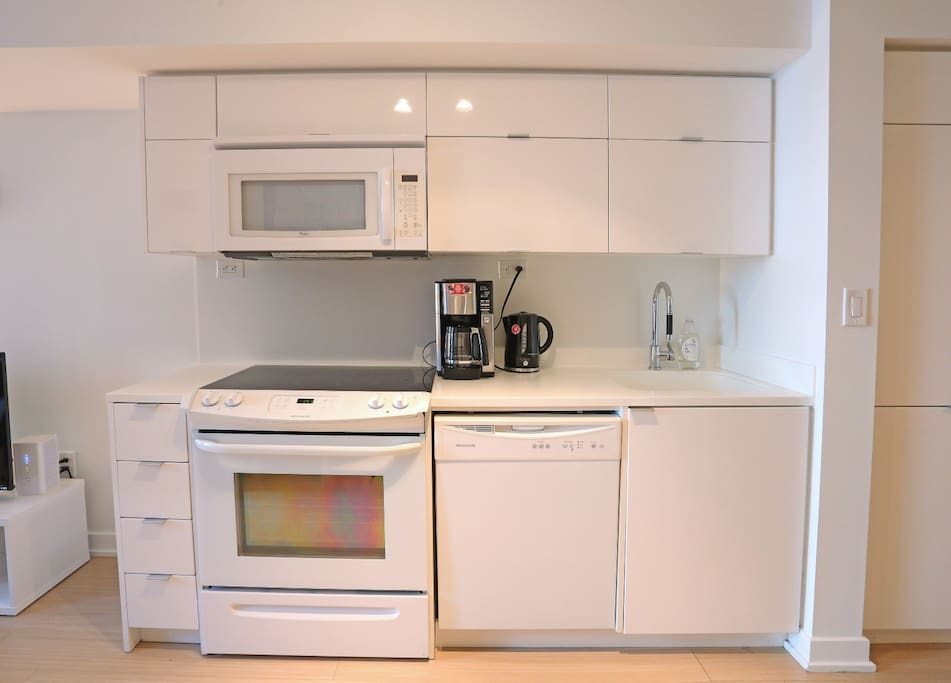 well stocked kitchen, with Microwave, Convection Oven, Dishwasher, Kettle, Coffee Maker and cabinets