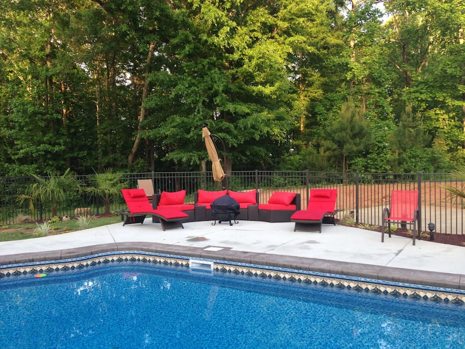 By the poolside, comfortable seating and a firepit.