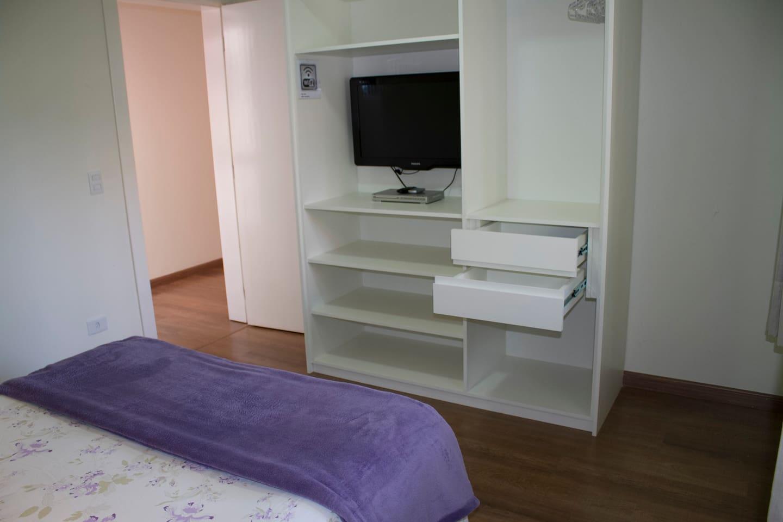 Quarto com TV e armários, incluindo roupa de cama.