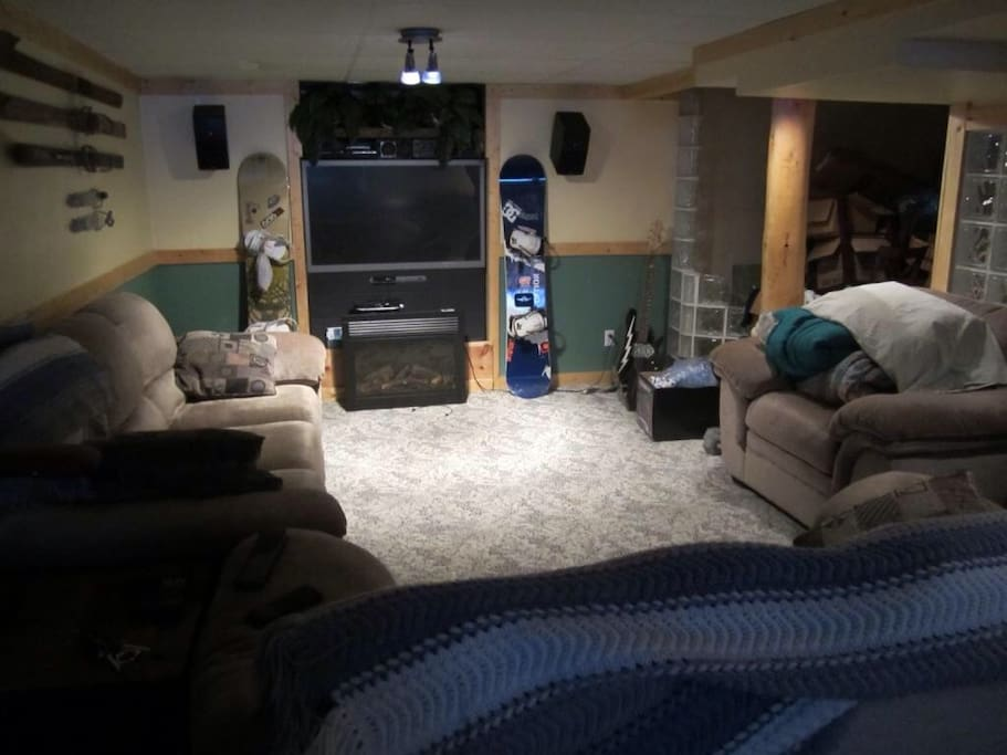 Basement for guests.  Canadian Mountain Lodge concept. Big  screen cable tv with surround sound DVD player , sofa bed, shuffle board table and mini fridge. No fireplace in basement