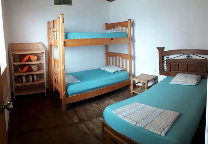 Habitación Grupal, cuenta con 3 Camas de plaza y media, velador y estante organizador para ropa u otros artículos personales .
