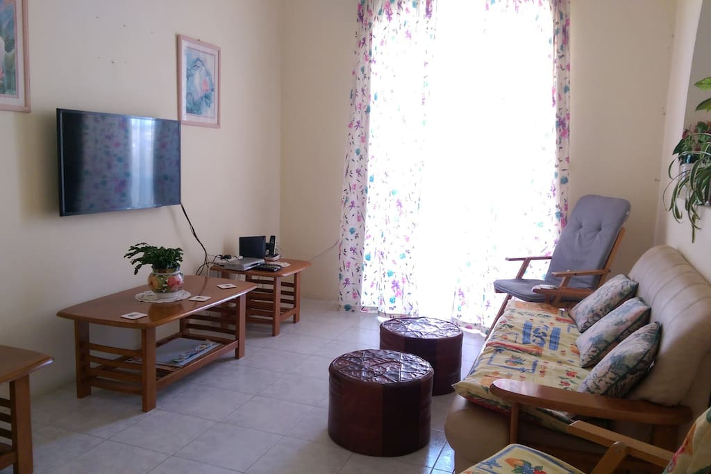Living area with smart TV leading to balcony with sea view