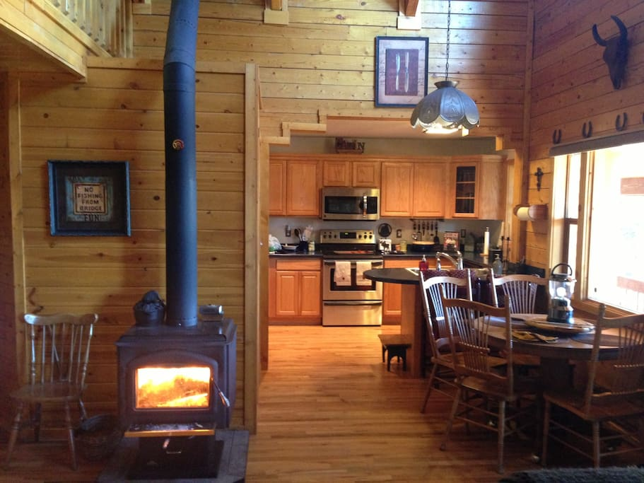 Wood burning stove with kitchen and eating area in the background. Kitchen stocked with everything you have at home to cook.