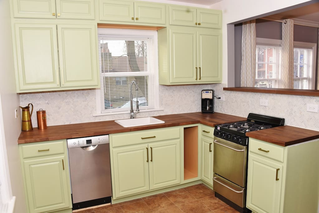 Newly remodeled kitchen with brand new cabinets, honed marble backsplash, butcher block countertops and stainless steel appliances