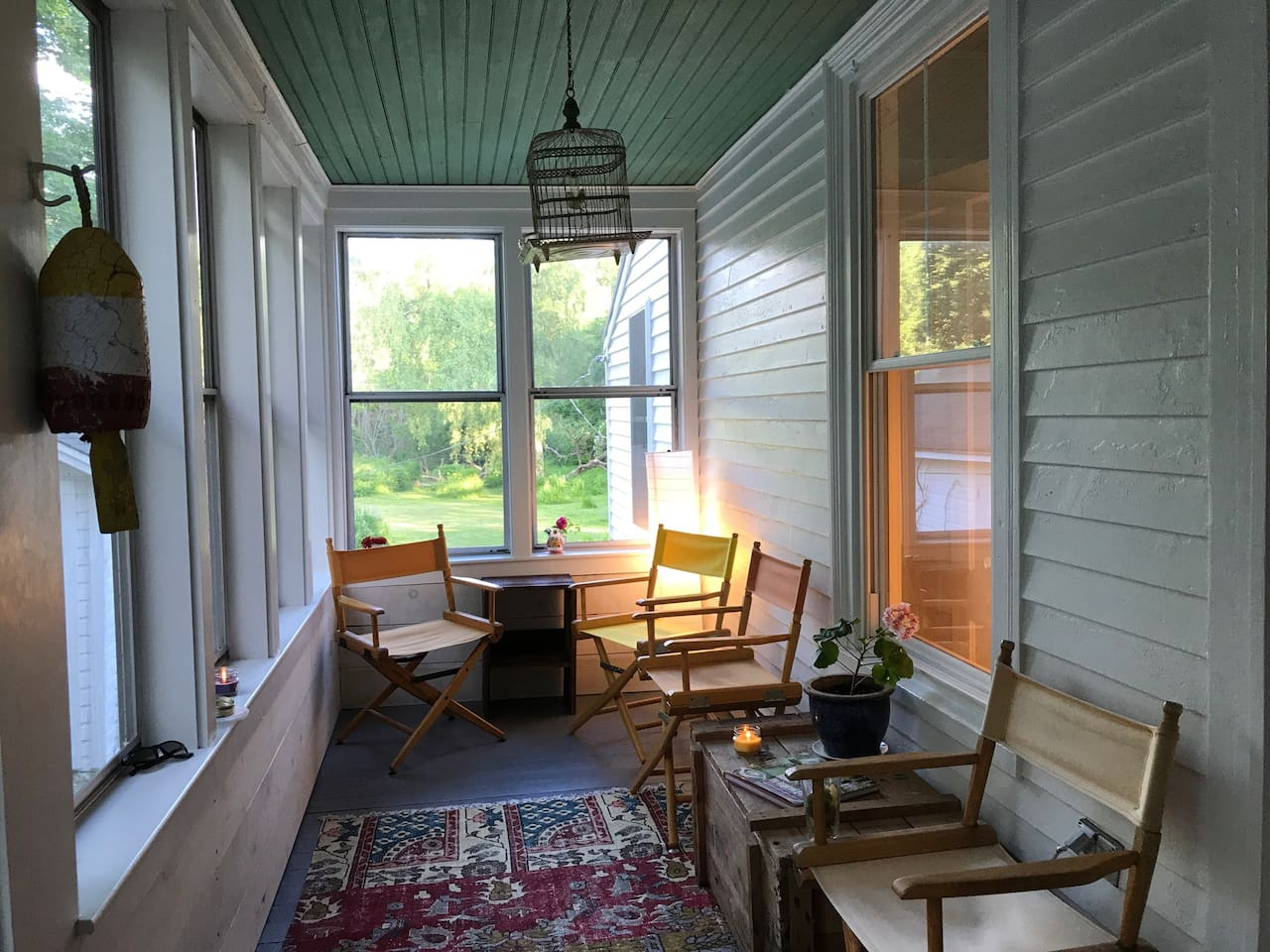 Screened porch off the kitchen looks out to large yard with wildflowers and meadow and is a lovely Spot to relax.