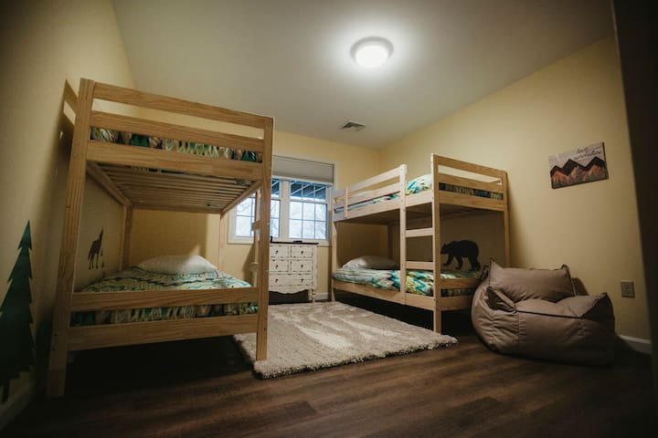 Bunk room can sleep 4 and has a reading nook with bookshelf and cozy chair