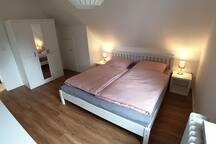 Schlafzimmer mit großem Doppelbett und Kleiderschrank