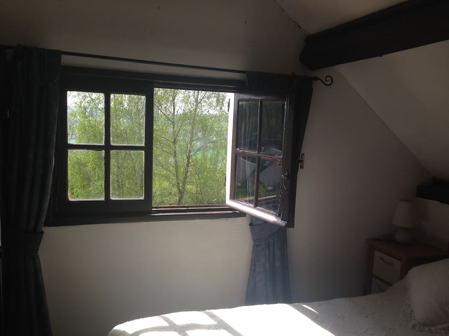 The bedroom has a view over the garden and the valley beyond.