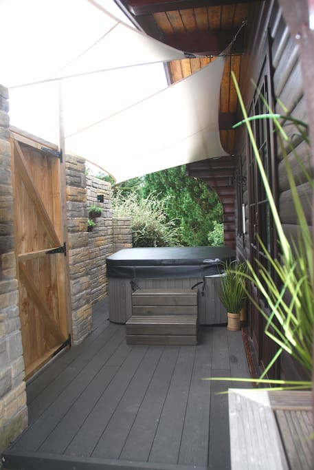 Composite decking, hot tub and sail shades for additional shelter and privacy