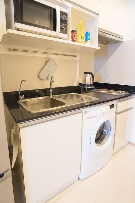 Kitchen area composed of:  1. Electrical stove and pan for light cooking 2. Microwave 3. Refrigerator 4. Thai seasonings 5. Tap water and Drinking water 6. Washing machine