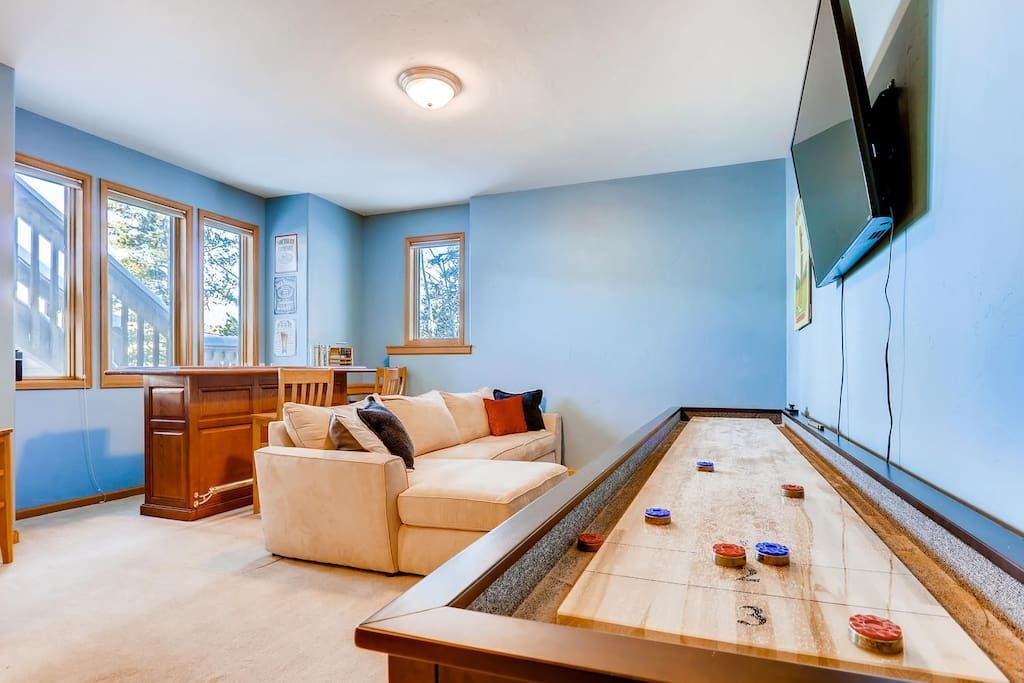 "Basement - including full oak bar, 55"" TV, and a brand new shuffleboard to keep everyone entertained"