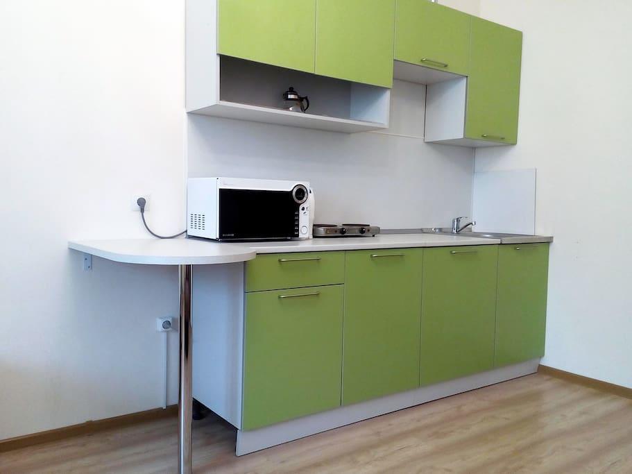 Кухня со встроенным холодильником и барным столиком