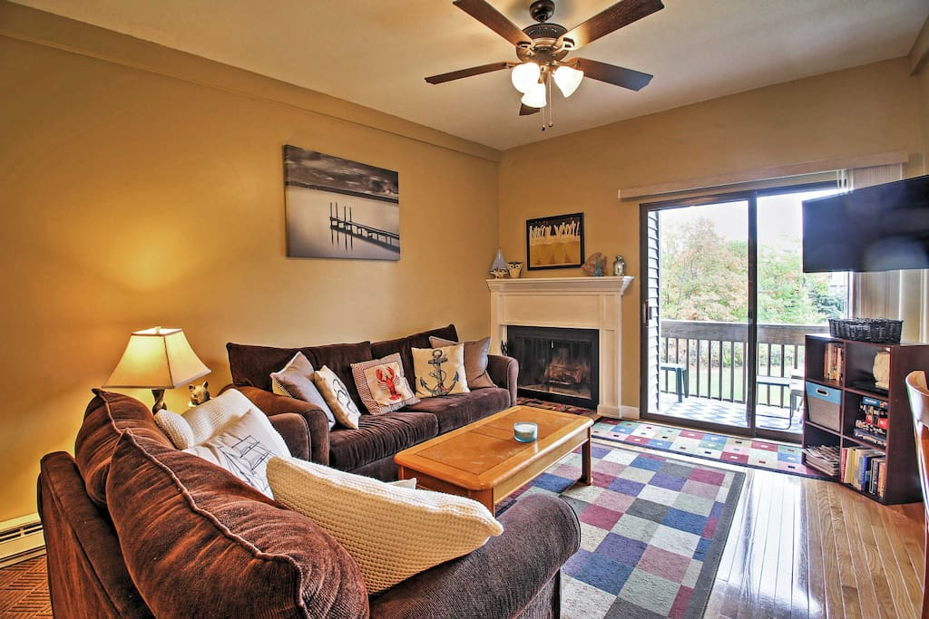 Living room with wood burning fireplace, balcony and ample seating