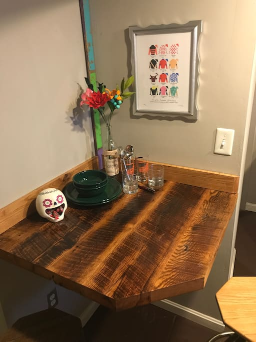 Reclaimed barn wood table, two stools, and local artwork