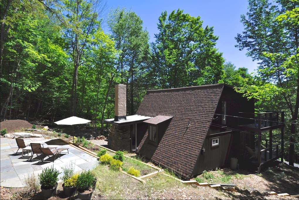 View of the back of the house. A deck and a stone patio