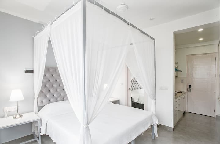 Four poster bed with White Flowing Chiffon Curtain