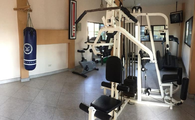 Air-conditioned gym with running and cycling machine, large range of free weights, tv, etc