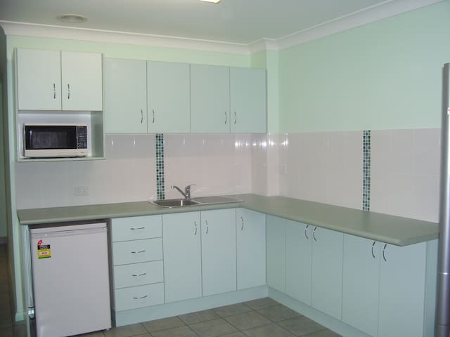Self contained kitchen with microwave, fridge, frypan, kettle, toaster, eating utensils