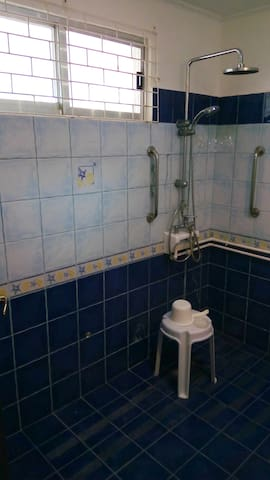 Large bathroom adjoining the master bedroom. This is the shower corner with hand rails to hold on to. Also toilet, sink and a cabinet with mirror are found here. Hot and cold water. High quality tiles. Screened window.