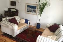 Lounge area with large windows overlooking front garden. Room includes TV with Apple TV (Netflix, iTunes ETA). WiFi access