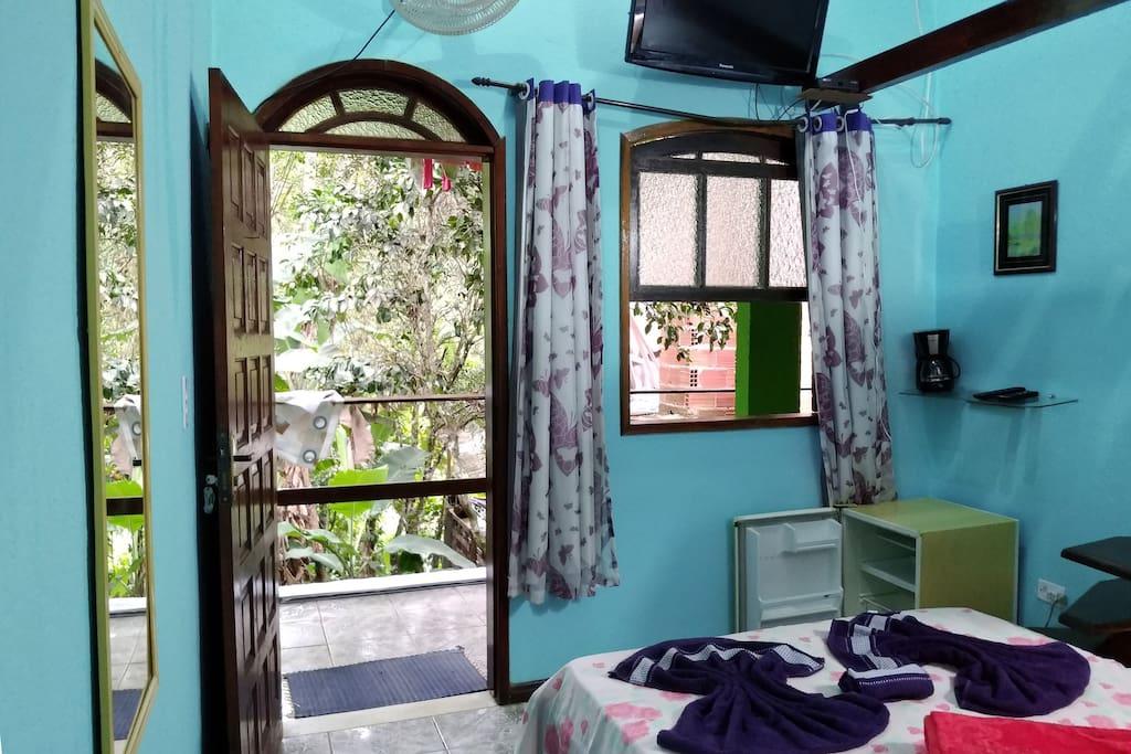 Primeiro piso com cama de casal, TV, frigobar e cafeteira. Ground floor with double bed, TV, mini-fridge and coffee machine.