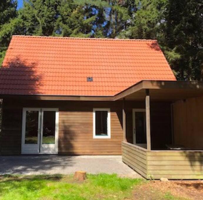Het vakantiehuis in het voorjaar met veranda en picknickbank (er zijn ook tuinstoelen aanwezig)