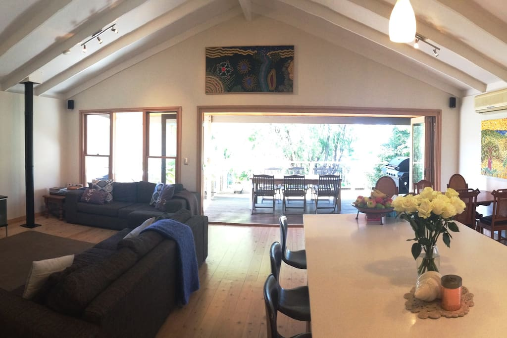 Upstairs open living/kitchen /dining area with bifold doors opening on to large entertaining deck