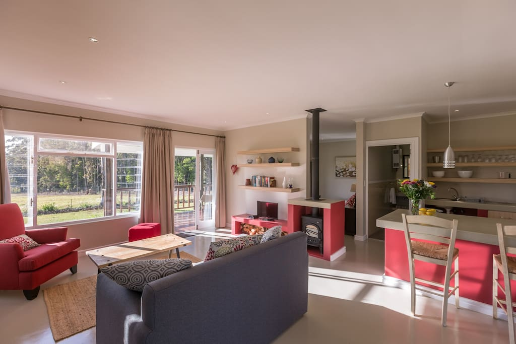 Open plan lounge and kitchen with large windows overlooking the gardens and farm.