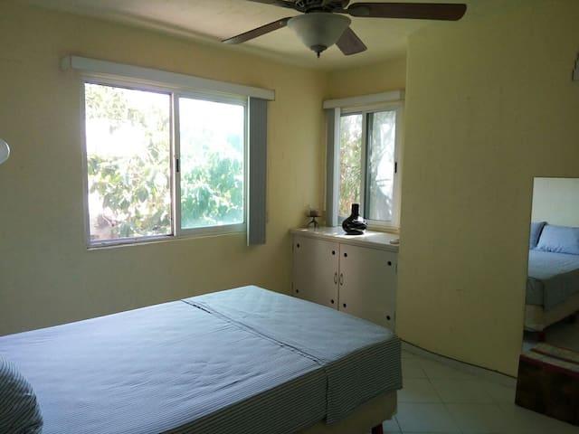 La habitación bien ventilada y sus dos ventanas con vista a la flora del edificio.